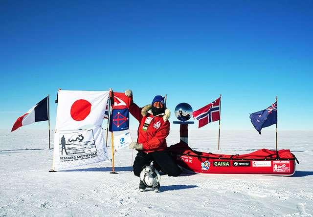 南極点で国旗や秋田県旗などを掲げる阿部さん