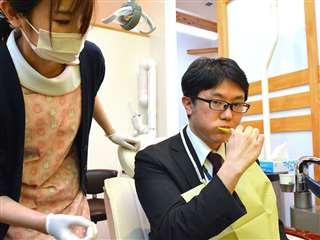 鈴木さん(左)に見てもらいながら、普段通り歯磨きをする記者=秋田市中通の安倍歯科医院