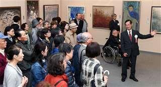 昨年の「春の院展・秋田展」で作品を解説する同人(右)と来場者たち=2018年4月25日、秋田市のアトリオン
