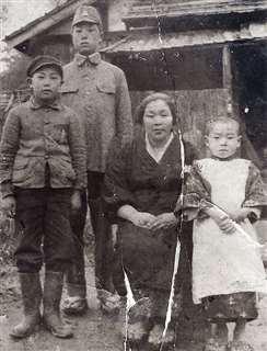 下浜の自宅前で母や2人の兄と(右端)