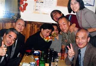 コンサートの打ち上げで友川さん(中央)を囲み盛り上がる(後列右から2人目)