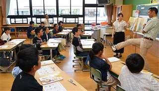 6年生に英語の絵本を読んで聞かせる町田准教授(右)。ボールを蹴るふりなど身ぶり手ぶりを交えて内容を伝える=由利本荘市の由利小学校、2019年5月