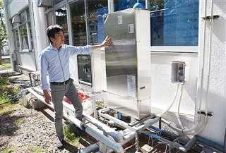 藤井教授が触れているのがヒートポンプユニット。2階にある研究室の冷暖房用に使われる=秋田市の秋田大手形キャンパス