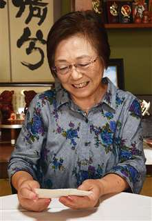 大好きな両親の写真を手に、2人への思いを語る眞野さん