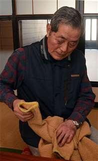 妻玲子さんが編んだカーディガンを手にする勇さん。長く着ているので少し色がくすんでいる