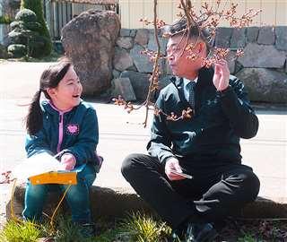 桜のつぼみを観察する沙和さん。担任の越後谷先生は時折「寄り道」しながら、丁寧に教える=4月、能代市の常盤小学校