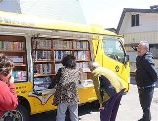 「かづの号」の本を吟味する地域の人たち。その様子を、工藤さん(右)が笑顔で見守る