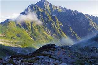 男性が登山中に撮影した北アルプスの剣岳。手前に見えるカラフルなテント群の中に、男性の1人用テントもある=2014年8月