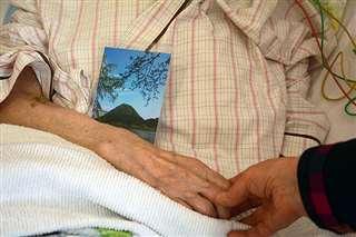 病室のベッドで、母の手を握るタミ子さん。母の胸元には「守り神」の山の写真がある