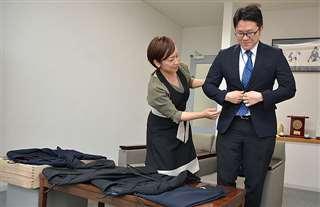 なかなか捨てる踏ん切りがつかず、スーツの前ボタンを締めようとする記者。左は柳瀬さん