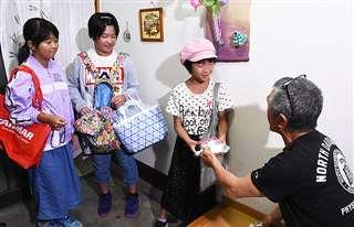 住民から豆やお菓子をもらう能代市の栗山地区の児童たち=9月13日
