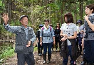 保育士の研修で森の大切さを説明(左)=今月3日、秋田市下浜羽川の「健康の森」