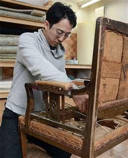 修理に持ち込まれた古い椅子を直す加藤さん