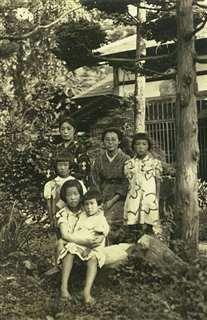 戦時中、家族と自宅庭で。最前列で妹を抱っこ