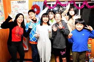 英語教室内で開いたクリスマスパーティーで、生徒と写真に納まる東海林さん(左)=昨年12月27日