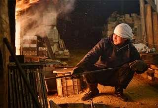 作陶に使う上薬を作るため、窯で稲わらを燃やす佐藤さん