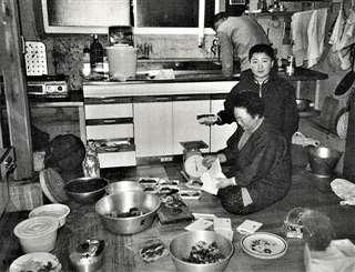持ち帰ったクマの肉を小分けする母英(手前)、父金作(奥)と長男大地=平成2(1990)年ごろ