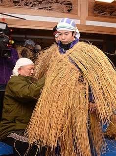 主演の仲野さん(右)にケデを着せる安田さん=1月28日、男鹿市船越