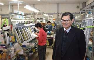 組み立て工程が行われている中藤電機産業の工場内を案内する保坂さん。「秋田で稼働するのが楽しみ」と話す=2月14日、愛知県津島市