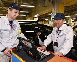 完成した車両の検査を行う社員と話す佐々木さん(右)=3月4日、愛知県豊田市のトヨタ本社