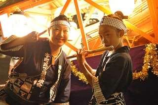 2年前の竿燈まつりで笛を吹く楓子さん(右)。最終日に佐々木さん(左)が見に来てくれた=2018年8月、秋田市の竿燈大通り(左近さん提供)