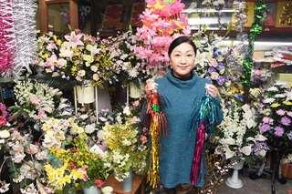 本町五丁目竿燈会の佐々木さん。手にしているのは、竿燈まつりの屋台に使われる装飾品=秋田市大町の佐々木造花店
