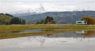 鳥海山と由利鉄の列車の両方が、水を張った田んぼに映り込んでいる。田植え前の一時期しか見られない風景だ=久保田~前郷駅間