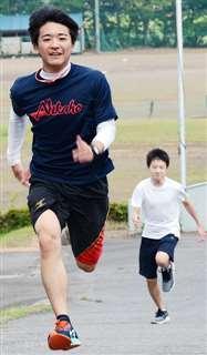 学校敷地内の坂を駆け上がる新田(左)