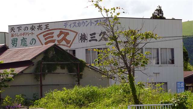 「天下の安売り王」という言葉が目を引く。脇本駅から徒歩数分の場所にある雑貨店「三久」の宣伝文句が、店近隣の数軒の建物にも書かれている
