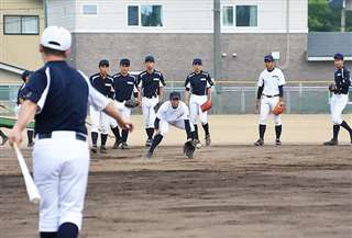 工藤監督(左)からノックを受ける能代松陽の選手たち=同校グラウンド