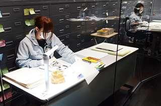 「マンガの蔵展示室」で保存作業を行うスタッフ