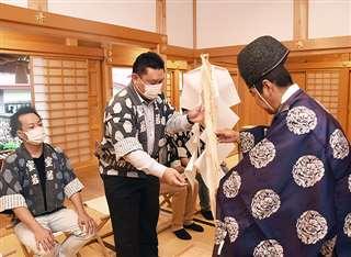 おはらいを受けた御幣を受け取る工藤さん(左から2人目)=秋田市千秋公園の八幡秋田神社