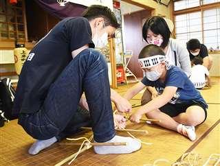 大人に手伝ってもらいながら親竹に横竹を結び付けた