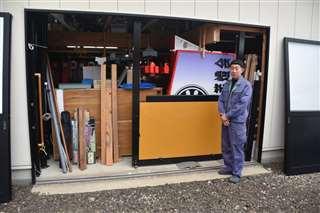 竿燈まつりの屋台に使う資材が詰まった倉庫の前に立つ相馬さん=15日、秋田市新屋松美ガ丘南町の「相馬看板」
