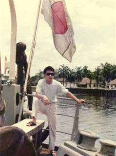 船員時代、サングラスを掛けて甲板でポーズを取る