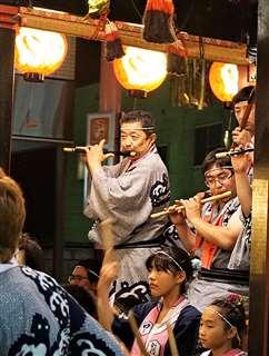 花輪ばやしで屋台に乗って笛を吹く川村さん(中央)=2018年8月(本人提供)