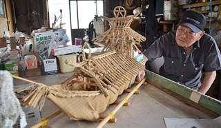 屋形舟の模型を眺める加賀谷さん。送り盆まつりで使われる舟作りに携わり60年以上になる