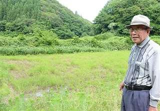 昨秋、最後に収穫した田の前に立つ加藤さん。今は草に覆われている