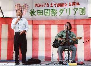 園長のバトンタッチを発表後、余興でステージに立つ(左)=開園25周年式典