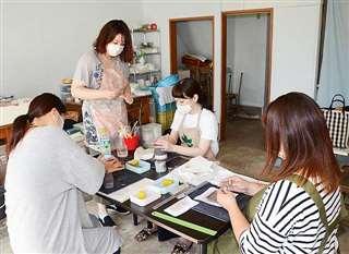 陶芸教室の参加者に練り込みの魅力を伝える草彅さん(左から2人目)=秋田市新屋のシェアアトリエ