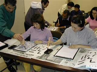 教室で習字の練習をする生徒たち