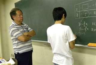教室で数学を指導する元高校教師の夫(左)