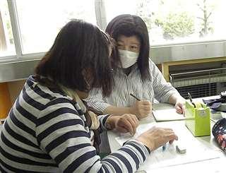 教室で日本語を指導するボランティア(右)