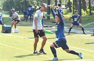 体力トレーニングに励む選手を見て回る吉田監督(中央)=9月、秋田市