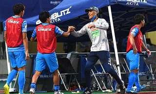 今月3日の岩手戦に競り勝ち、選手とタッチする吉田監督(右から2人目)。珍しく喜びを爆発させた=秋田市