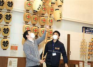 秋田市大町の市民俗芸能伝承館「ねぶり流し館」で竿燈を手にするアドテックシステムの社員(県提供)