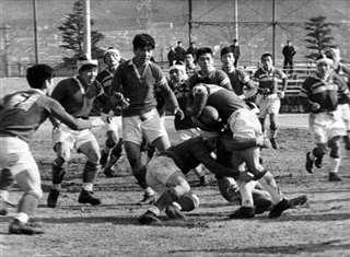 1967年1月の準々決勝でタックルする秋田の選手(中央下)。勝って準決勝に進んだ=花園ラグビー場