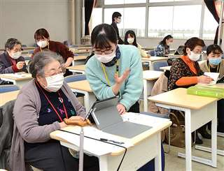 学生からタブレット端末の操作方法を学ぶ参加者=先月19日、秋田市の秋田大本道キャンパス
