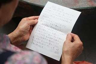 逮捕された女からの手紙を手にする女性(写真の一部を加工しています)