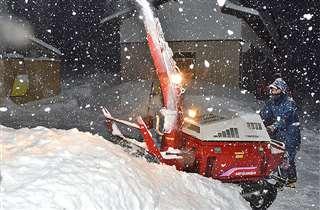 同居する長男と一緒に隣家の玄関前を除雪する阿部高美さん(手前)=1月30日午前6時20分ごろ